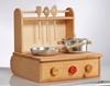 Petite cuisinière en bois avec 3 boutons, 1 rouge et 2 en bois naturel. Sur le dessus, 2 plaques de cuisson portant 1 poêle en aluminium avec manche en bois et une casserole avec poignées en bois et un bouton en bois sur  le couvercle. A l'arrière se trouve une parois en bois avec une étagère pour pendre les ustensiles qui en se refermant permet de porter la cuisinière et d'y ranger les jouets.