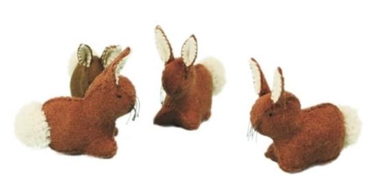 Vier bruine konijnen met witte staart in wolvilt.