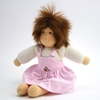 Sitting doll with brown mohair hair, brown hair, a white t-shirt with long sleeves and a pink pinafore dress.