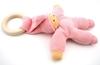 Poupée rose en coton bio avec anneau de dentition en bois couchée sur le dos.