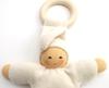 Close up klein wit babypopje in bio katoen, gevuld met bio wol, met houten bijtiring, handgeschilderd gezicht.