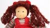 Close up op het gezicht van een voddenpop met donker bruin wollen haar met twee staartjes en rode strikken. De pop heeft handgeschilderde blauwe ogen en draagt een gestreepte T-shirt met lange mouwen en een rood fluwelen kleed.
