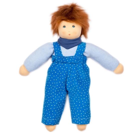 Jongensvoddepop met rood mohair haar en blauwe ogen.  Hij draagt een fel blauwe overal met witte stippen, een lichtblauwe sweatshirt en donkerblauwe halsdoek.