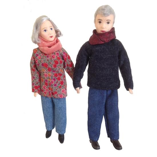Poppen voor poppenhuis, grootouders. De grootvader draagt een blauwe wollen broek, een donkerblauwe trui en een bordeaux sjaal. De grootmoeder draagt een lichtblauwe wollen lange broek , een zalmroze zijden sjaal en een lange  vest met rode en roze bloemen.
