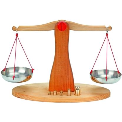 Houten  weegschaal in natuurhout en oranje middenstuk en aan elke kant een inox schaaltje opgehangen door 3 rode koordjes. Vooraan een rij koperen gewichten.
