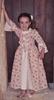 Petite fille souriante portant une robe de princesse blanche avec des bouquets de roses en impression, une sous-jupe blanche, 2 rubans blancs sur les manches longues et 3 rubans fleuris sur la poitrine dans le style de Madame de Pompadour.