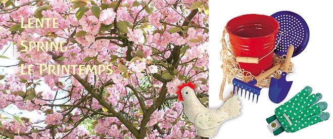 Cerisier du Japon en fleur, à côté un set de jeux de sable, une paire de gants de jardinage verts pour enfants et une petite poule blanche en feutre.