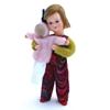 Klein meisje, poppenhuis popje met blond haar, een strikje, een veelkleurige lange broek en een groene trui. Ze draagt een roos popje in haar armen.