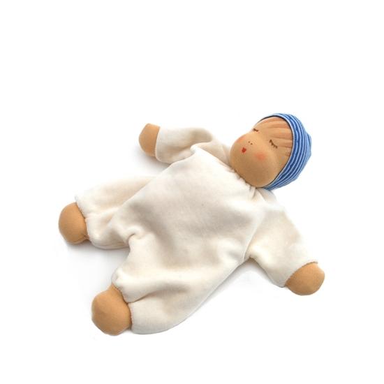 Slapende pop in ivoorkleurige bio katoenen badstof met handjes, voetjes en gezichtje in huidkleurige tricot en met een lange pinnemuts in donkerblauw en lichtblauw gestreepte tricot.